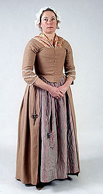 model wearing warm brown bodice and skirt over irredescent pinkish petticoat
