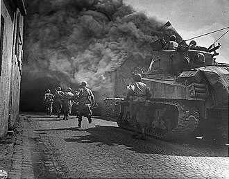 file:/activities/oralhistory/cappics/cohen1944_tank, alt: Tank and American soldiers charging down a street of Wernberg, Germany