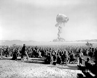 file:/activities/oralhistory/cappics/elliot1945_detonation, alt: thousands of sitting soldiers watch a mushroom cloud in the distance