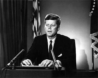 file:/activities/oralhistory/cappics/elliot1945_kennedy, alt: president kennedy speaking from a podium