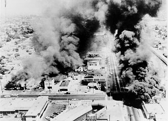 file:/activities/oralhistory/cappics/elliot1945_watts, alt: an aerial view of several burning buildings