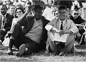 file:/activities/oralhistory/cappics/romer1963_blackwhite, alt: two protesters--one black, one white, sharing the shade of a placard